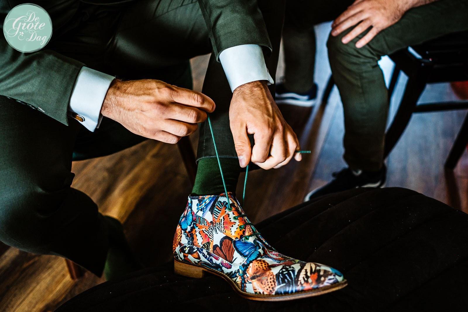 Mosgroen trouwpak met klassieke das en trendy schoenen