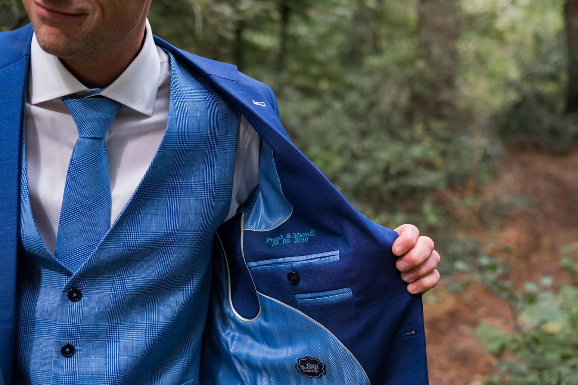 Blauw trouwpak met geruite gilet en geruite das
