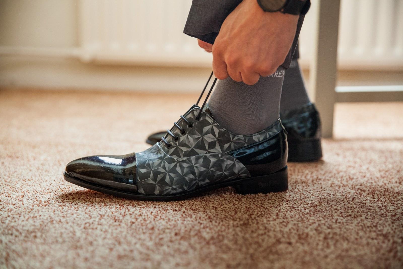 Grijs trouwpak vol kleur met geblokte gilet en bijzondere schoenen