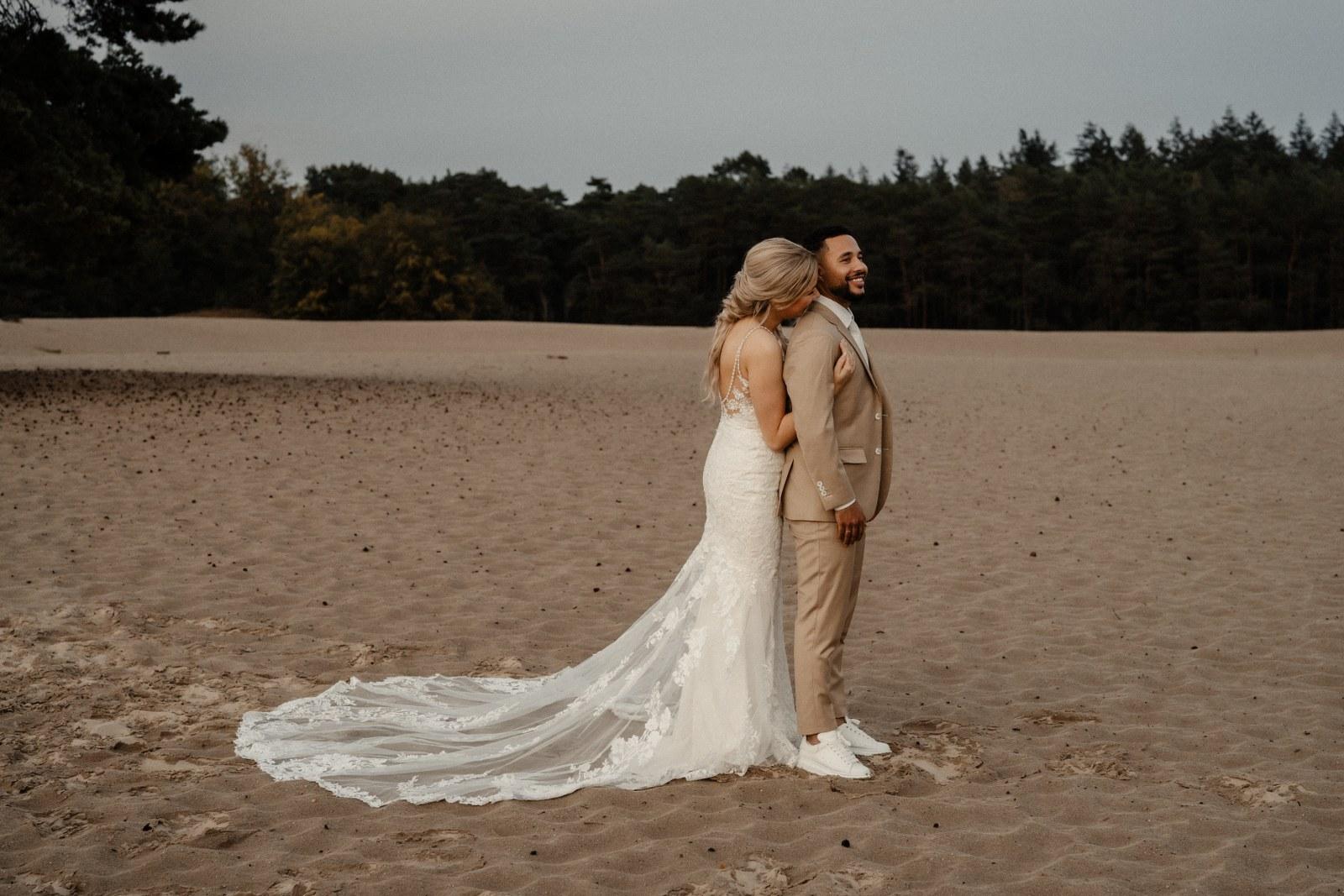 Sneakers, strak in beige trouwpak met double-breasted gilet