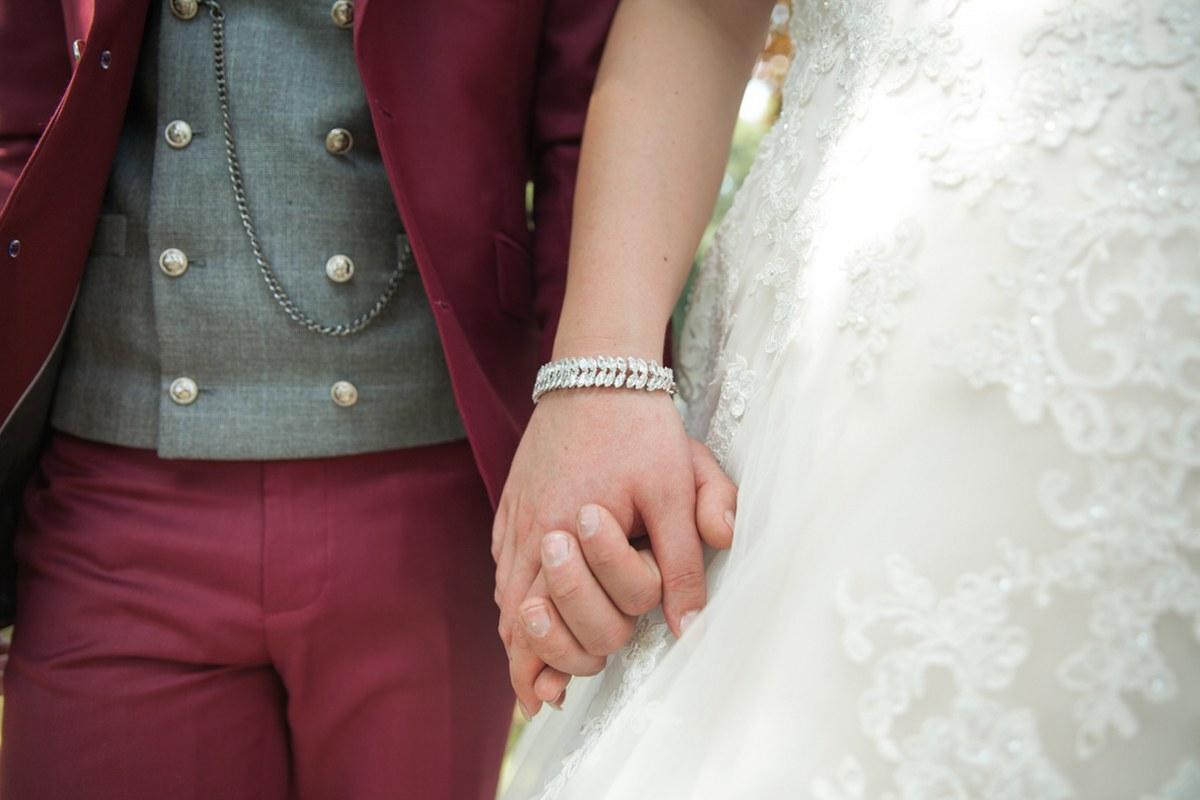 Rood trouwpak, grijze gilet en bijzondere knopen