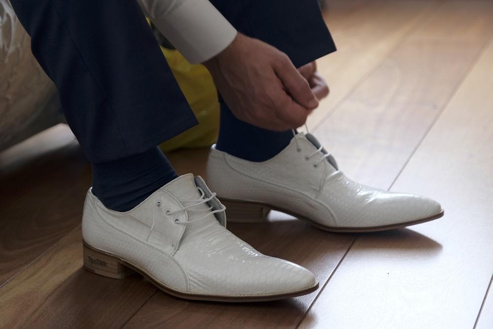 Donkerblauw trouwpak, witte knopen, witte schoenen